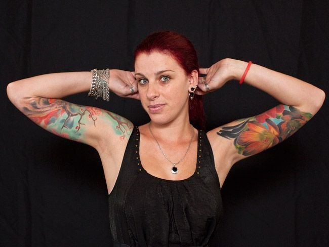 На руке рука с татуировочной машинкой